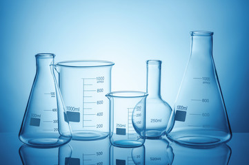 Laboratory glassware set with reflections on blue background