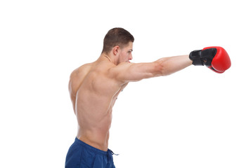 A sports guy boxer with a bare torso and gloves is working out a blow. Isolated.