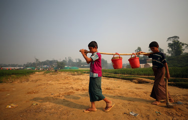 Rohingya refugee children carry buckets of sand through Balukhali refugee camp near Cox's Bazar