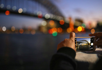 A tourist takes a photograph on their iPhone of the Sydney Harbour Bridge at sunset on a spring day in central Sydney