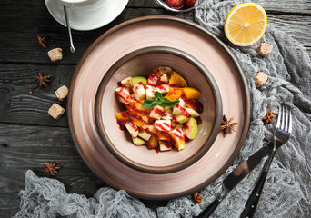 fruit salad with sauce in a ceramic plate with a cup of tea on a wooden background