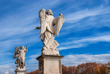 Angels statues with clouds in autumn. Two 17th century baroque masterpiece at the top of Sant'Angelo Bridge in Rome