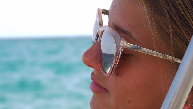 Beautiful young girl in the sunglasses in the sea