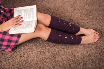 Young woman reading book and legs with warmers on carpet floor. Close up