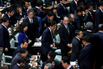 Japan's PM Abe walks to cast a ballot at the Lower House of the Parliament in Tokyo