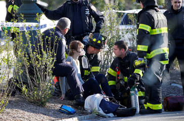 A woman is aided by first responders after sustaining injury on a bike path in lower Manhattan in New York