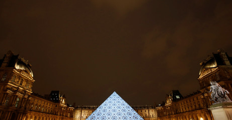An image depicting the roof of the new Louvre Abu Dhabi museum is projected on the Louvre Pyramid in Paris