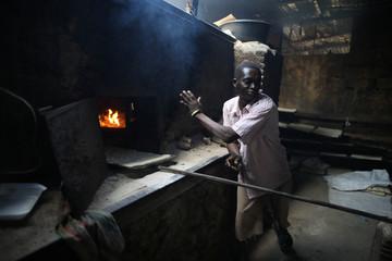 A man puts pieces of dough inside an oven at a bakery in Port-au-Prince