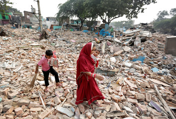 A family walks amid the rubble of homes in a slum which was razed to the ground by local authorities in a bid to relocate the residents, in Delhi