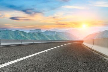 Asphalt highway and mountain nature landscape at sunset