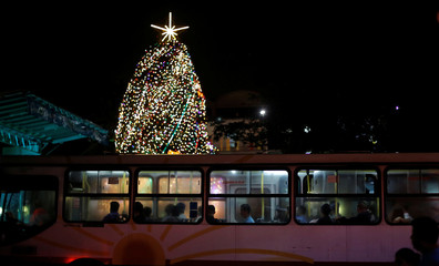 A bus passes in front the Christmas tree lighting ceremony at the Children's Hospital in San Jose