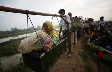 Toyeba, a 45-year old Rohingya refugee woman, is carried as she continues to make her way after crossing from Myanmar into Palong Khali, near Cox's Bazar