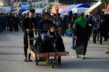 Boys push a cart with women during the commemoration of Arbain in Kerbala