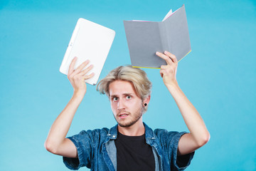 Man student holding tablet and book.