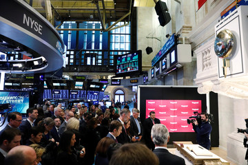 Members and guests of the New York Stock Exchange bow their heads in reverence to the victims of a recent attack in New York