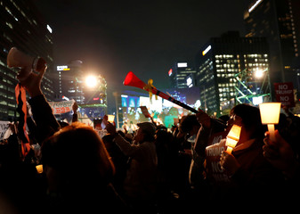 Anti-Trump protesters shout against U.S. President Donald Trump's motorcade as it drives past while heading to South Korea's presidential Blue House, in central Seoul