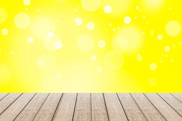 Wood table with yellow color background with bokeh.