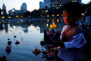 A boy dressed in traditional Thai clothes prepares to place a krathong into a pond at a public park during the Loy Krathong festival in Bangkok