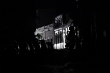 A woman holds a flashlight while standing on a street in the dark, after Hurricane Maria hit the island and damaged the power grid in September, in Old San Juan