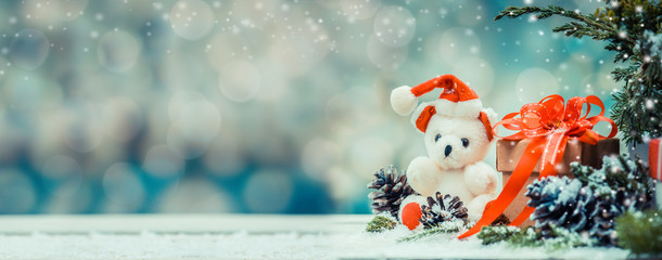 Christmas decoration on snow with Teddy bear and gift box. Copy space for text with bokeh blur background.