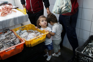 A Libyan child looks at fish in a plastic basket at the fish market in Tripoli