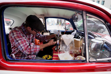 Matthew Pendleton uses brewing equipment in his 1968 VW Bug converted into a coffee cart in downtown Denver