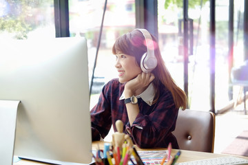 Happy woman using desktop computer while listening at studio office.