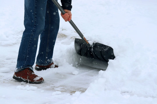 Winter snowy day background. Man shoveling snow on driveway during a heavy snowfall. Close up composition.