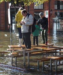 "People take photos at the Fish Market flooded during stormy weather caused by a storm called ""Herwart,"" in Hamburg"