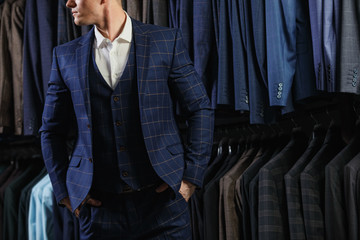 client is elegant guy in jacket. In the background classic suits and jackets