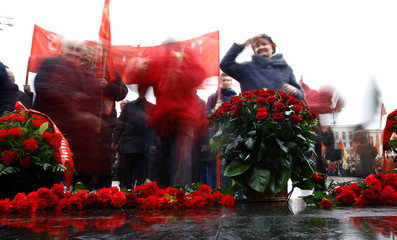 People take part in a wreath laying ceremony at a monument of the Soviet state founder Vladimir Lenin at Independence Square in Minsk