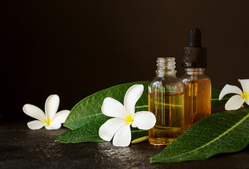 small glass jars with oil and Frangipani Plumeria patchouli flowers for spa treatments black background, selective focus