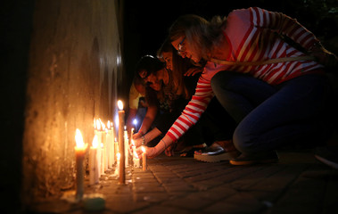 People place candles outside the Instituto Politecnico high school, where the five Argentine citizens who were killed in the truck attack in New York went to school, in Rosario
