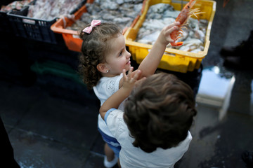 A Libyan child plays with a prawn at the fish market in Tripoli