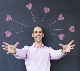 Single adult white man wearing a pink shirt with streched out arms standing in front of a blackboard with painted hearts. Concept of crazy love