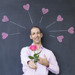Single adult white man wearing a pink shirt standing in front of a blackboard with painted hearts holding a rose. Concept of crazy love