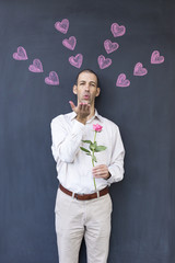 Single adult white man wearing a white shirt standing in front of a blackboard with painted hearts holding a rose. Concept of crazy love