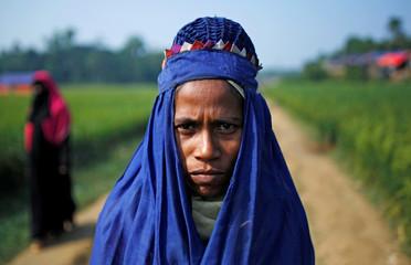 A veiled Rohingya refugee woman walks towards her shelter at Palong Khali refugee camp near Cox's Bazar