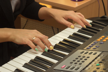 Fingers playing electronic piano keyboards