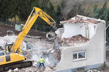 Baustelle mit Abriss eines alten Wohnhauses mit Bauarbeiter