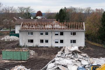 Baustelle mit Abriss eines alten Wohnhauses - Bauschutt im Vordergrund