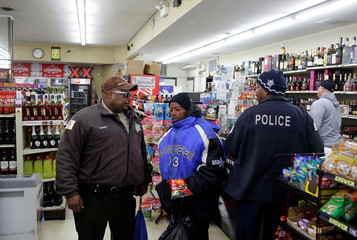 Officer Harris of the Cook Country Sheriff's office talks to a customer in Chicago