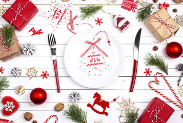 Festive table setting with cutlery and Christmas decorations on white wooden table. Top view.