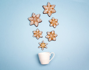 Snowfall from gingerbread snowflakes in a coffee cup on a blue background.