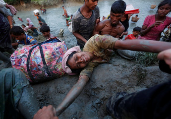 Photographers help a Rohingya refugee woman to come out of Naf river as they cross the Bangladesh-Myanmar border in Palong Khali, near Cox's Bazar