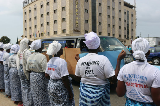 Women hold banners encouraging peace during a peace mediation meeting held by ECOWAS for Liberia's presidential run-off election, in the Sinkor neighbourhood of Monrovia