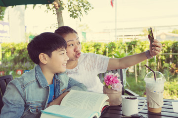 A young asian mother makes selfie with her little cute son at a table in a cafe.
