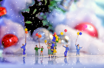 Miniature people with family holding balloon hang out in pine woods during winter.