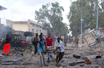 Civilians assist a man injured from a suicide car bombing at the gate of Naso Hablod Two hotel in Mogadishu