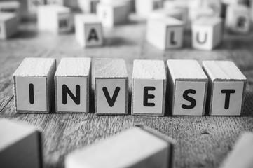 concept mot formé avec des lettres en bois - invest